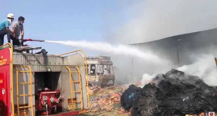 A fire truck deck gun is turned on the smoking remains of a tire recyling plant in India. - Screencapture Via YouTube