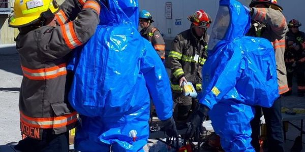 Haz mat responders suit up to enter a poultry processing plant in Ontario Sunday after leaking...