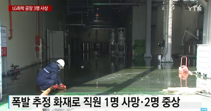 A worker removes water runoff after an explosion and fire Tuesday at a chemical plant in South Korea. - Screencapture Via YTN News