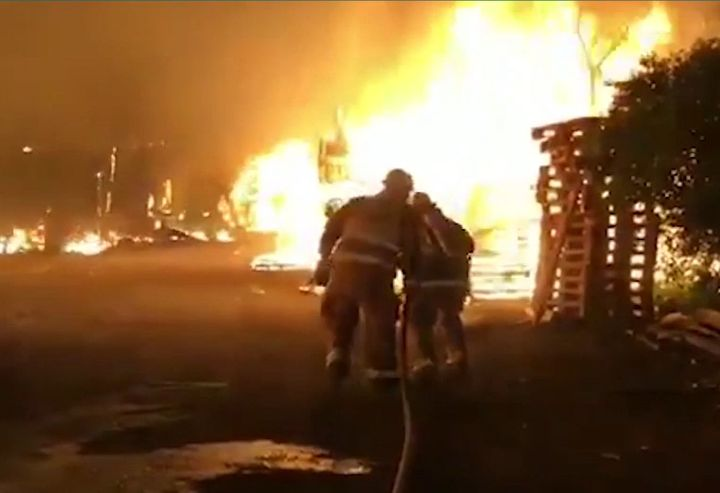Firefighters move in on flames at a pallet factory Monday in Mexico. - Screencapture Via Abstractor Noticias