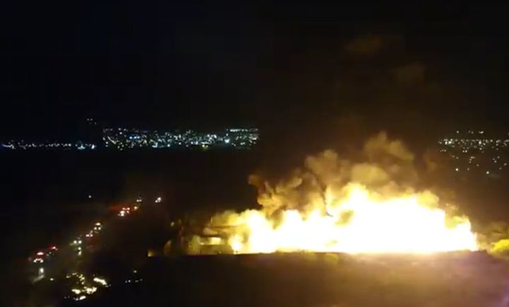 Flames from burning recycling plant dwarfs the city lights of Garcia in the background. - Screencapture Via Twitter