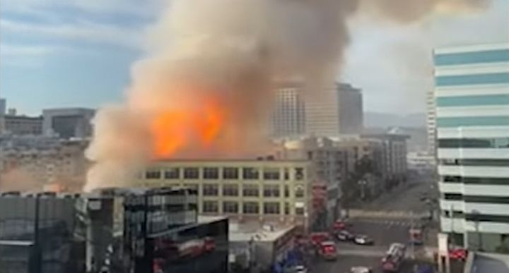Smoke and flames rise Saturday evening above downtown Los Angeles. - Screencapture Via Los Angeles Times