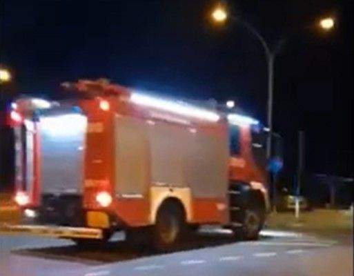 Fire truck racing to a fiberboard plant fire Wednesday in Poland passes motorist. - Screencapture Via YouTube