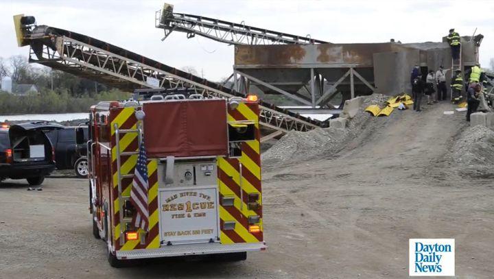 Rescuers struggle to reach a gravel pit worker buried inside a hopper Saturday. - Screencapture Via Springfield News Sun