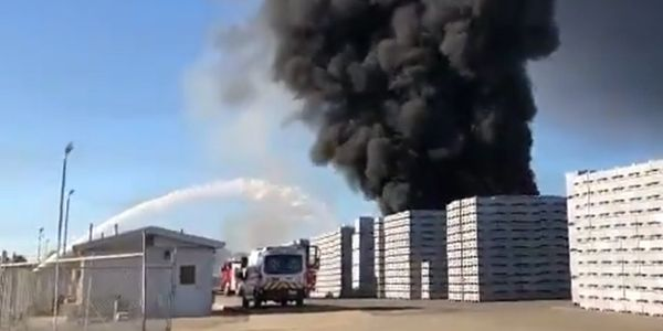 Black, choking smoke rises from acres of pallets outside a California packing plant.