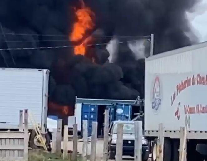 Flames break through the black smoke shrouding a burning seafood plant Thursday in Canada. - Screencapture Via Global News