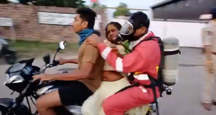 A rescue worker helps rush one of the injured to aid after a toxic gas release Thursday from a polymers plant in Visakhapatnam, India. - Screencapture Via TOI Vizag News