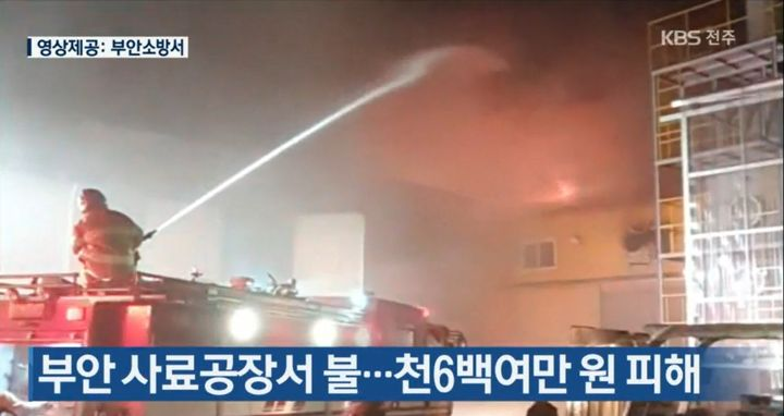 Firefighter attacks fire breaking through the roof of a feed mill Thursday in Buan, South Korea, - Screencapture Via KBS News