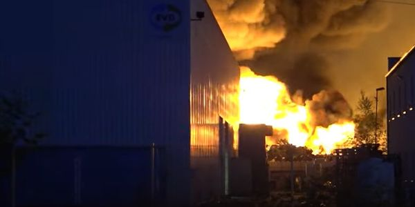 Billowing flames silouette surrounding buildings during a mammoth industrial fire in Diez,...