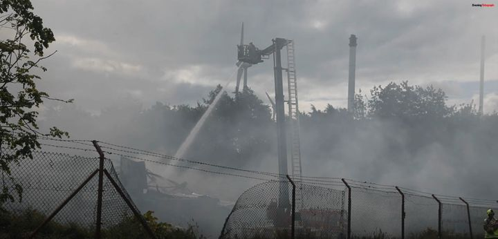 Water applied to the remailandns of a factory destroyed Sunday in Scotland. - Screencapture Via Evening Telegraph