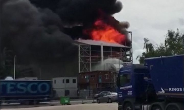Flames show atop a seed processing plant in southeast London Friday. - Screencapture Via Metro News