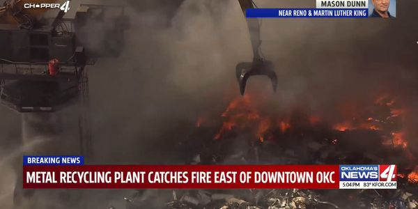 A heavy crane is used to separate burning material during a recycling plant fire Tuesday in...