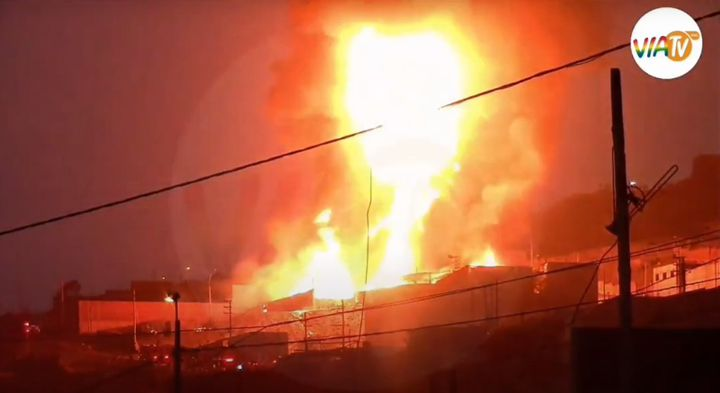 Flames billow above a burning paint factory in Peru Thursday. - Screencapture Via Via TV