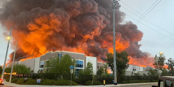 Flames rise above a warehouse distribution center Friday in Redlands, California.