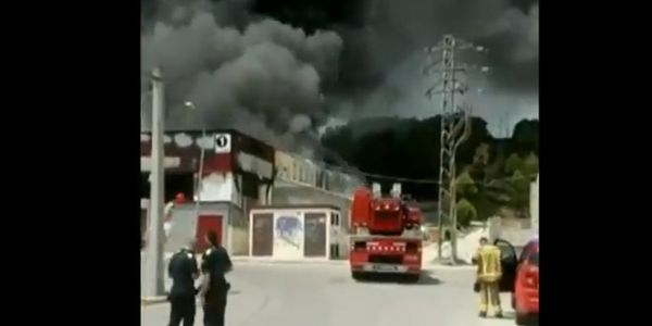 Thick black smoke dominates the sky above a food processing plant Sunday in Spain.
