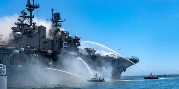 Port of San Diego Harbor Police Department boats combat a fire onboard USS Bonhomme Richard at...