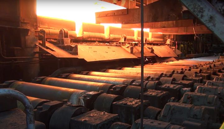 Rolled steel emerges from a furnace at ArcelorMittal's Indiana Harbor plant. - Screencapture Via YouTube
