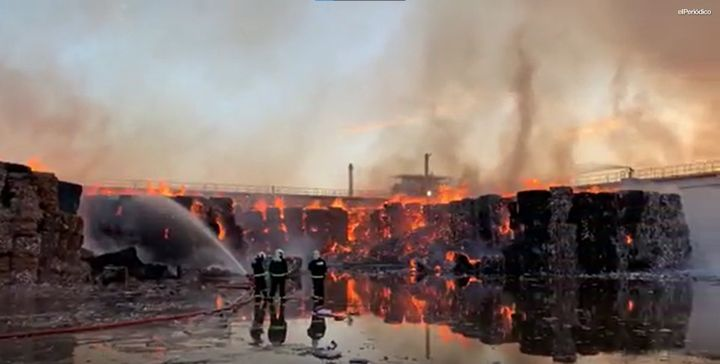 Bales of recycled paper burned Wednesday at a warehouse in Spain. - Screencapture Via el Periodico