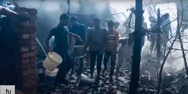 Worker form a bucket brigade to save what they can of a candle factory in India.