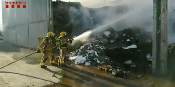 Firefighters attack burning paper stored outside a recycling plant in Spain.