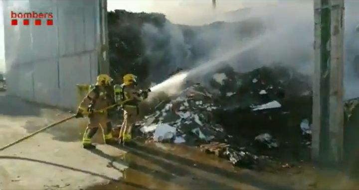 Firefighters attack burning paper stored outside a recycling plant in Spain. - Screencapture Via Generalitat de Catalunya Bombers