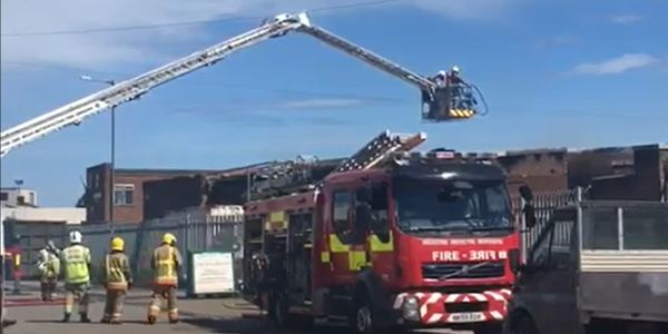 An aerial ladder is used to check the fire scene after a blaze at a UK manufacturing plant.