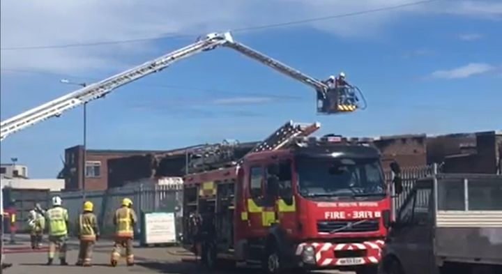 An aerial ladder is used to check the fire scene after a blaze at a UK manufacturing plant.  - Screencapture Via Chronicle Live