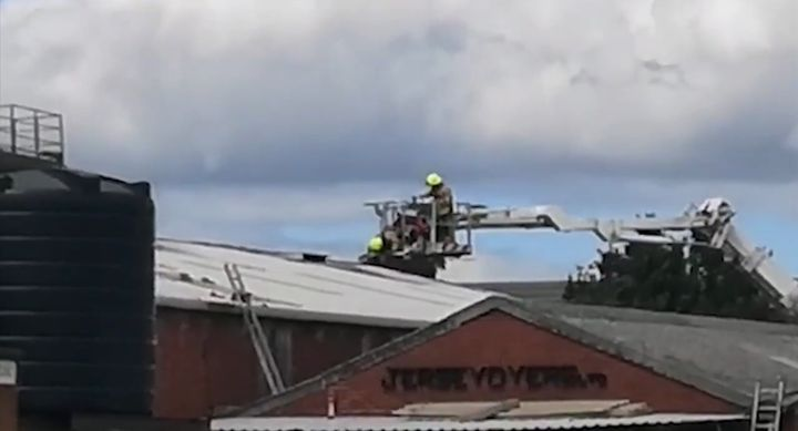Local firefighters use two aerial ladders to reach a roof fire Tuesday at a dyeing factory in England. - Screencapture Via Leicestershire Live