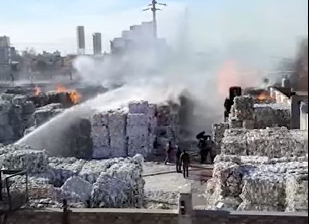 Flames consumed baled paper waiting to be recycled at a plant in Argentina. - Screencapture Via YouTube