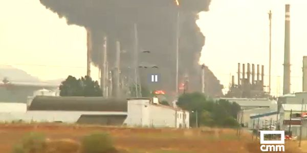 Two storage tanks burn at an oil refinery in Spain Monday.