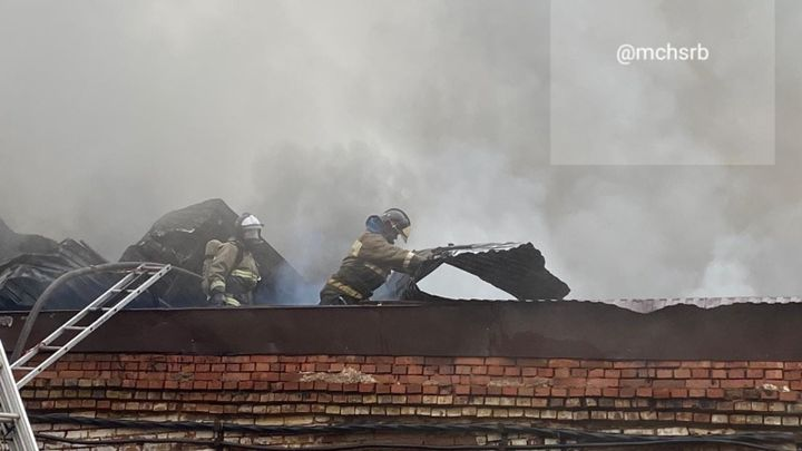 Firefighters work on the roof of a burning brick plant Saturday in Russia. - Photo Courtesy of EMERCON