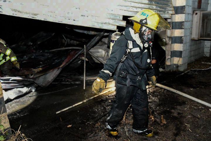 Firefighters follow up after a fire at a former battery plant Sunday in El Salvador. - Photo Courtesy of Secretaria de Prensa de la Presidencia