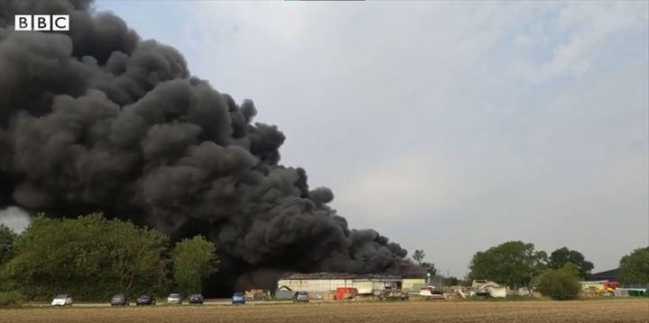 Smoke rises from a plastic injection molding factory in southeast England Thursday. - Screencapture Via BBC