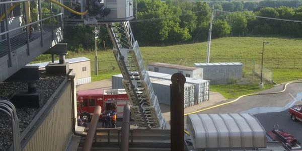 Firefighters used an aerial device to reach a burning air conditioning unit atop a factory in...