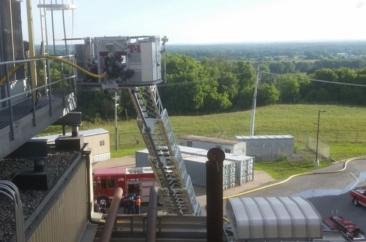 Firefighters used an aerial device to reach a burning air conditioning unit atop a factory in New York state Wednesday. - Photo Courtesy of Lowville Fire Department