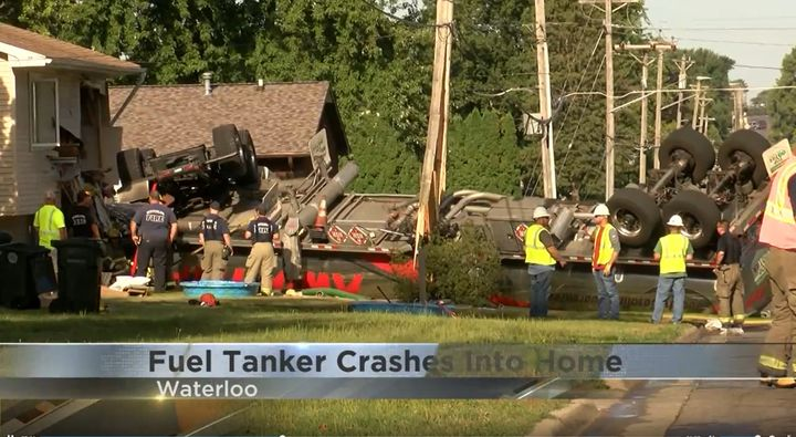 A big rig hauling diesel ended up overturned in a homeowner's yard after a wild ride through Waterloo, Iowa, Thursday. - Screencapture Via KWWL