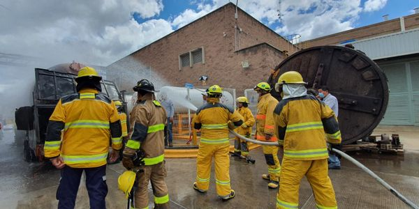 Firefighter push into the yard of a tannery in Mexico to extinguish escaping propane.