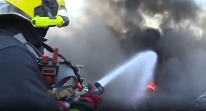 A firefighter works close to the heat in a warehouse fire reported Tuesday in China. - Screencapture Via NMG News