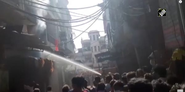 Delhi residents attempt to control the flames during a plastics factory fire in India Saturday.