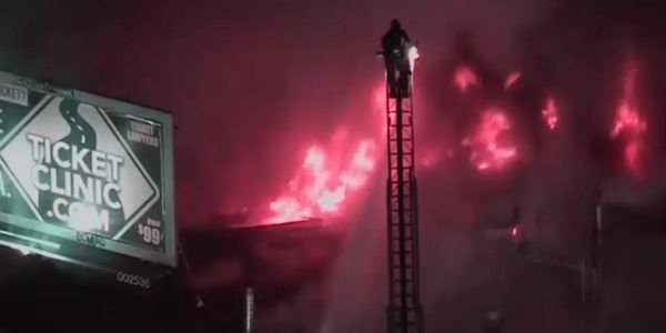 Flames burst through the roof of a dry cleaning plant in Los Angeles Tuesday morning.