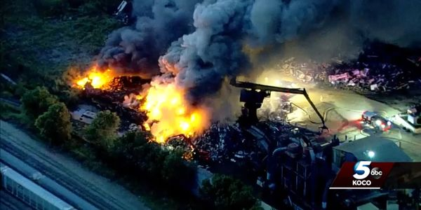 Firefighters use heavy equipment to separate burning material Tuesday morning at a Oklahoma City...