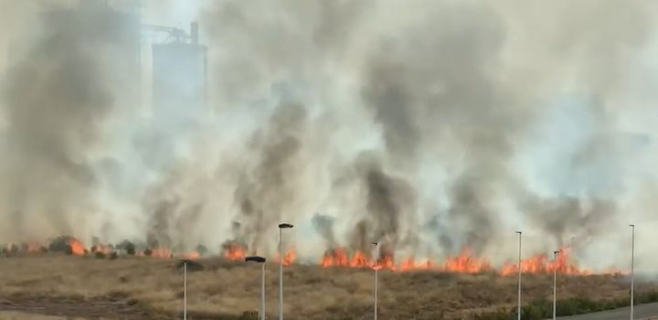 Smoke from wildfire Wednesdayall but obscures a Spanish cement plantin the distance. - Screencapture Via El Periodico de Aqui TV