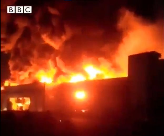 Flames consume a two-story dairy complex near Tehran. - Screencapture Via BBC