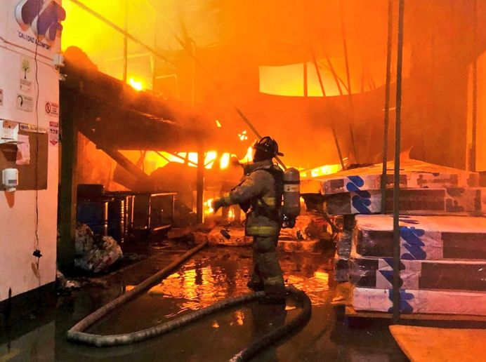 Firefighter enters a burning mattress factory Wednesday in Bogota, Colombia. - Photo Courtesy of Bomberos de Bogota