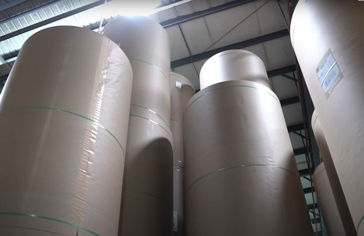 Giant rolls of corrugated paper waiting to be used. - Screencapture Via YouTube