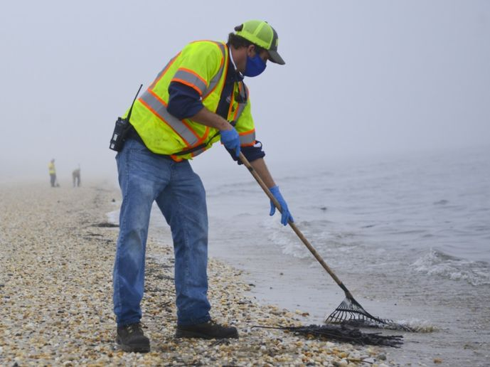A member of a contracted oil spill response organization cleans oily debris from Slaughter Beach in Delaware as part of the Broadkill 2020 oil spill response. - Photo by Petty Officer 3rd Class Isaac Cross, U.S. Coast Guard District 5