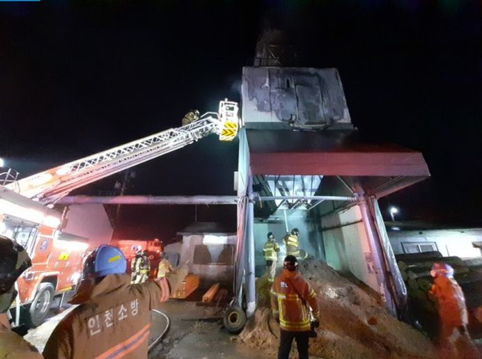 Firefighters use an aerial device to reach a burning dust collector Friday at a South Korean sawmill. - Photo courtesy of Incheon Western Fire Department