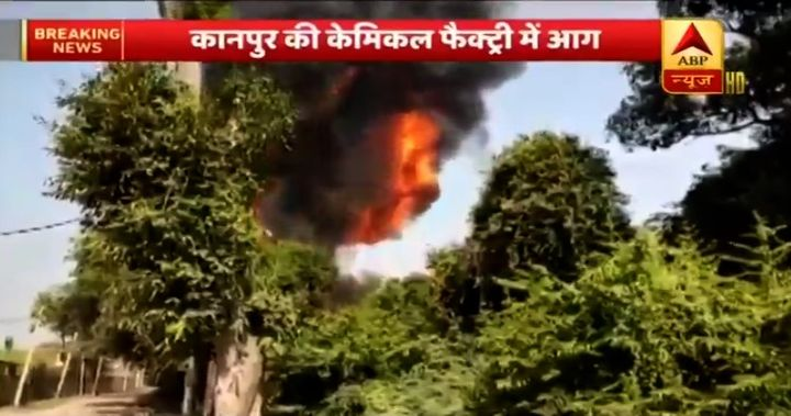 Flames from a paint factory fire rise above the surrounding trees Monday in India. - Screencapture via ANI