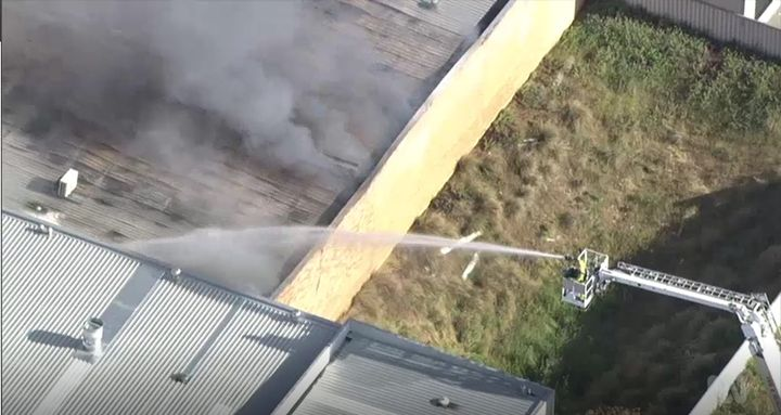 Firefighters pump water into a burning soap factory Friday in Melville, Australia. - Screencapture Via ABC Australia