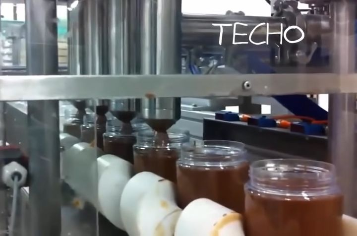 Bottles of Nutella being filled on the assembly line. - Screencapture Via Techo